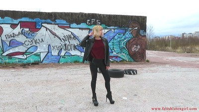 Sexy blonde Eva walks in leggings on a wasteland and shows her tight ass